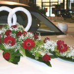 2 Trauringe als Symbol der Hochzeit im Blumengesteck. Diese Variante eignet sich besonders gut für die Fahrzeuge mit großen Motorhauben.